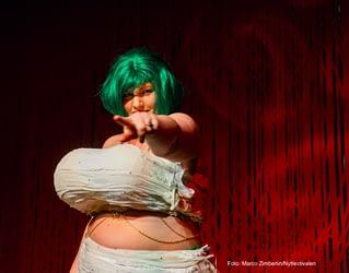 Burlesquedanser med grønt hår og ballongpupper peker mot deg